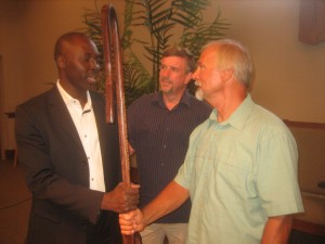 Calvin Greiner, an intercessor, presents a shepherd's staff to Nemi Chigoji, ARC chair, representing the broader Mennonite Church. Lancaster Mennonite Conference Bishop Lloyd Hoover looks on. PHOTO CREDIT: Richard Showalter