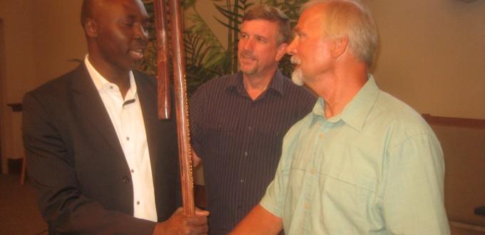 Calvin Greiner, un intercesor, presenta un cayado a Nemi Chigoji,  Presidente del ARC, en representación de la iglesia menonita más amplia. Un obispo de la Conferencia Menonita de Lancaster, Lloyd Hoover, observa. CREDITO POR LA FOTO: Richard Showalter.